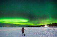 Paseo en moto de nieve bajo la aurora boreal
