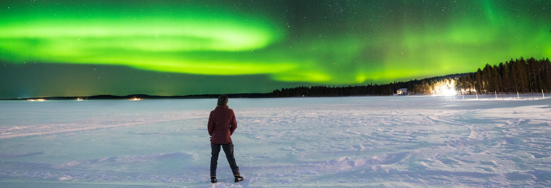 Passeio de moto de neve sob a aurora boreal