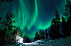 Paseo en trineo de perros husky bajo la aurora boreal